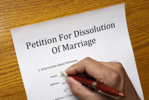 Forms for a divorce on a table, male hand with pen is starting to fill out the form